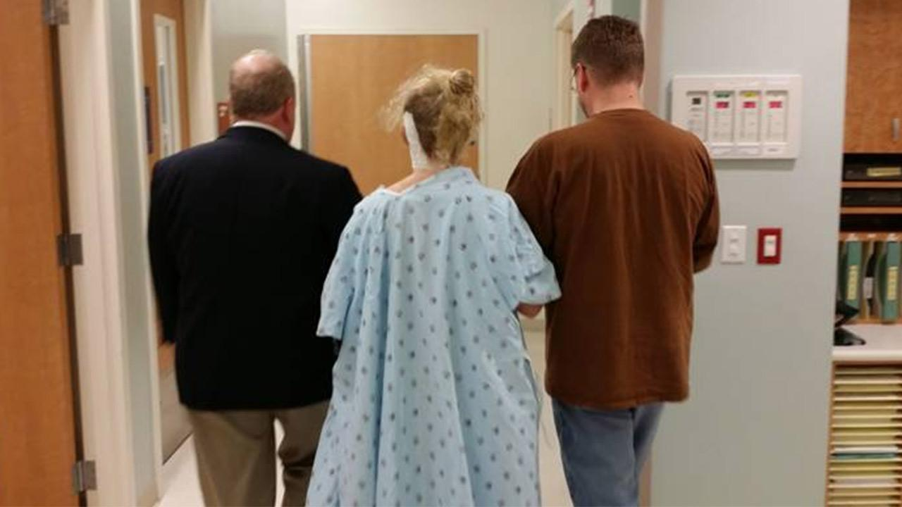 KatieRose Hamilton, a 13-year-old girl living with a painful condition known as trigeminal neuralgia, is seen walking with her doctor and her father following surgery.
