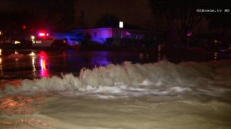 Water gushes down the street near the 700 block of Pomona Street in Santa Ana, following a water main break on Friday, March 7, 2014.