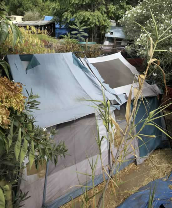 A tent and shacks are shown in the backyards of...