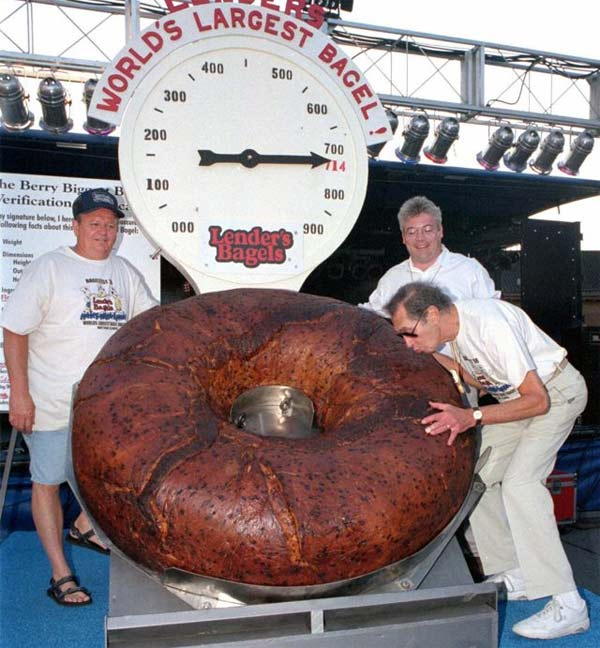 In this July 24, 1998 photo, Murray Lender kisses the world&#39;s largest bagel while baker Larry Wilkerson, left, and Lender&#39;s Bagel Bakery manager Jim Cudahy watch after the weight of the bagel was revealed during Bagelfest in Mattoon, Ill. Lender died at a hospital in Miami from complications from a fall on Thursday, March 22, 2012. He was 81 years old. <span class=meta>(Associated Press)</span>