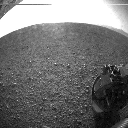 This is one of the first images taken by NASA&#39;s Curiosity rover, which landed on Mars the evening of Sunday, Aug. 5, 2012 PT &#40;morning of Monday, Aug. 6, 2012 ET&#41;. It was taken through a &#39;fisheye&#39; wide-angle lens on the left &#39;eye&#39; of a stereo pair of Hazard-Avoidance cameras on the left-rear side of the rover. The image is one-half of full resolution. The clear dust cover that protected the camera during landing has been sprung open. Part of the spring that released the dust cover can be seen at the bottom right, near the rover&#39;s wheel. On the top left, part of the rover&#39;s power supply is visible.  Some dust appears on the lens even with the dust cover off.  <span class=meta>(NASA&#47;JPL-Caltech)</span>
