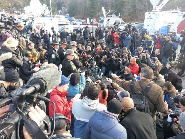 Media crowd Connecticut officials holding a news...