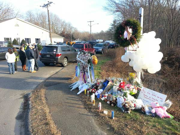 A makeshift memorial of flowers, candles and toys was set up on the side of the road leading up to Sandy Hook Elementary School, where a gunman opened fire Friday, killing 26 people, including 20 children, before turning the gun on himself.