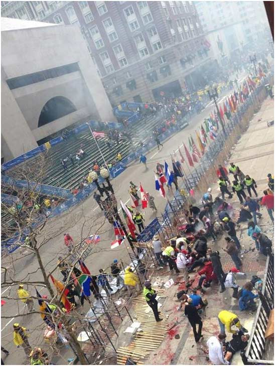 Two bombs exploded near the finish of the Boston Marathon on Monday, killing two people and injuring 23 others.  About two hours after the winners crossed the line, there was a loud explosion on the north side of Boylston Street, just before the photo bridge that marks the finish line. Another explosion could be heard a few seconds later.  Competitors and race volunteers were crying as they fled the chaos. Bloody spectators were being carried to the medical tent that had been set up to care for fatigued runners. Authorities went onto the course to carry away the injured while stragglers in the 26.2-mile race were rerouted away from the smoking site. <span class=meta>(Courtesy of Tyler Wakstein)</span>