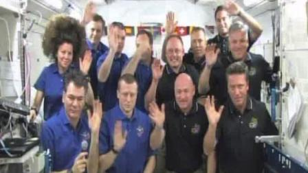 This image provided by NASA television shows the crews of the space shuttle Endeavour, in black shirts, and the International Space Stations Expedition 27 wave goodbye after speaking with Pope Benedict XVI at the Vatican Saturday May 21, 2011.