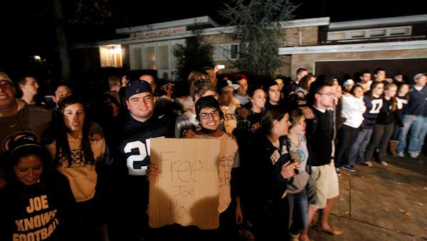 Students greet Penn State football coach Joe Paterno as he arrives at his home, Tuesday, Nov. 8, 2011, in State College, Pa.