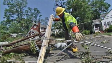 A utility worker is seen picking up a downed power line in an East Coast neighborhood in this photo. Deadly summer storms killed over a dozen people and left millions without power in June 2012.