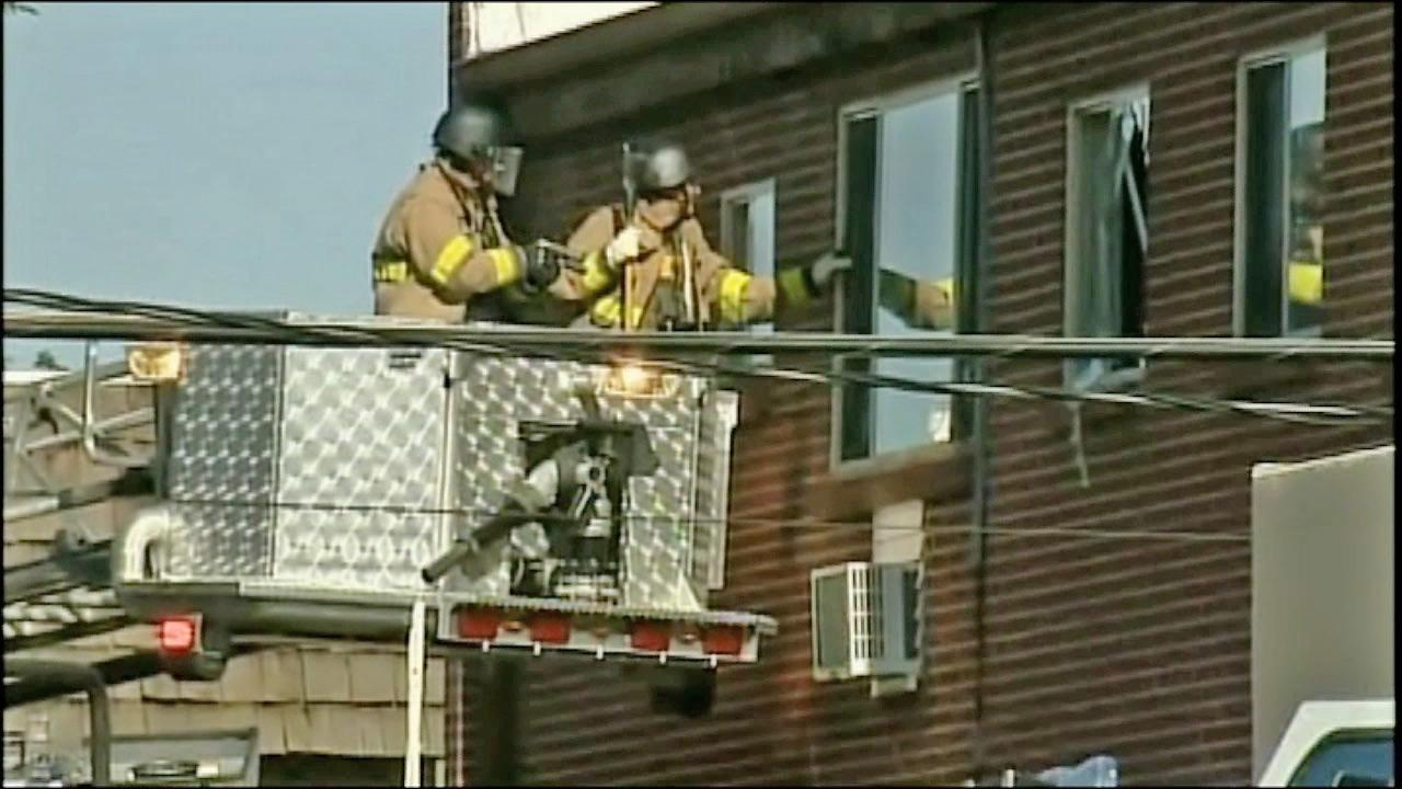 Officials are seen outside the window of James Holmess apartment in Colorado on Friday, July 20, 2012, where a large amount of explosives was reportedly found, prompting officials to proceed with caution.
