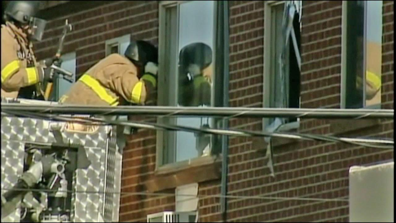 An official is seen peeking inside the window of James Holmess apartment in Colorado on Friday, July 20, 2012, where a large amount of explosives was reportedly found, prompting officials to proceed with caution.