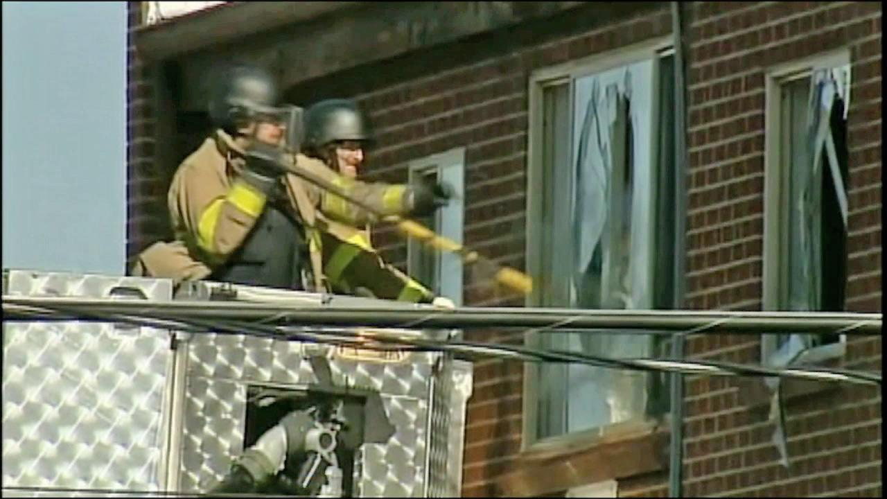 An official is seen breaking the window of James Holmess apartment in Colorado on Friday, July 20, 2012, where a large amount of explosives was reportedly found, prompting officials to proceed with caution.