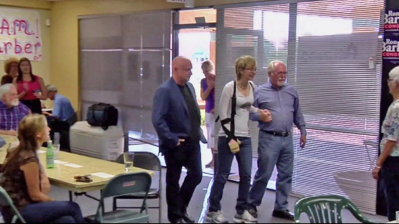 Gabby Giffords (center) is seen walking beside her husband, retired astronaut Mark Kelly (left), in this undated file photo.