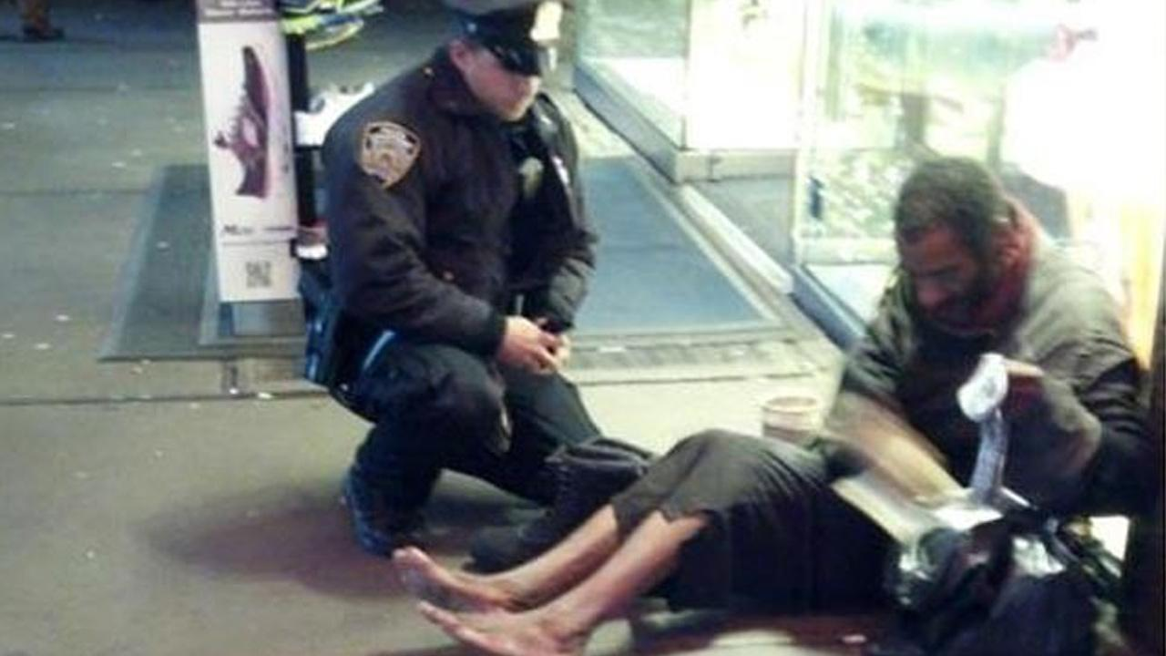 An NYPD officer gives a shoeless homelsess man a pair of boots in New York City, Nov. 27, 2012.