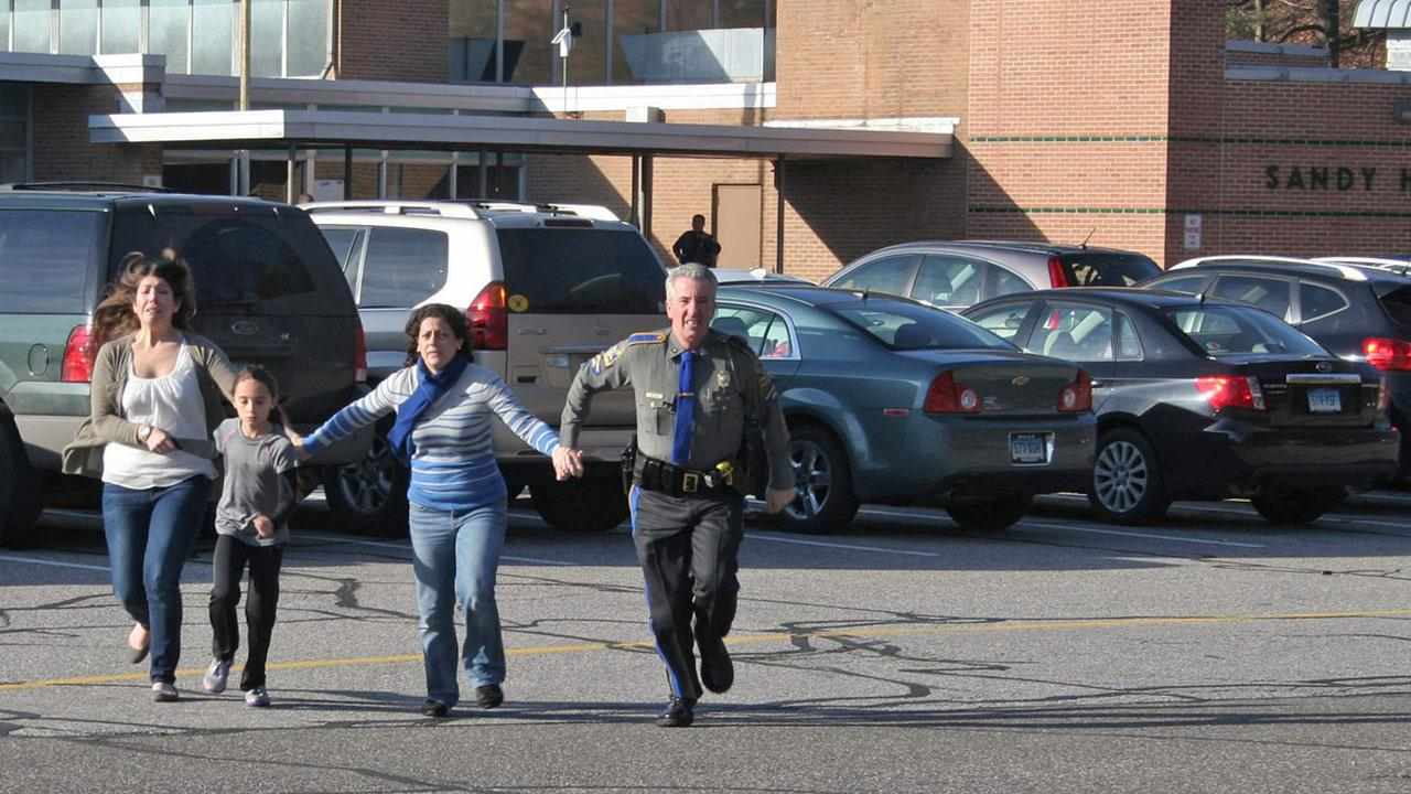 In this photo provided by the Newtown Bee, a police officer leads two women and a child from Sandy Hook Elementary School in Newtown, Conn., where a gunman opened fire, killing 26 people, including 20 children, Friday, Dec. 14, 2012.Newtown Bee, Shannon Hicks