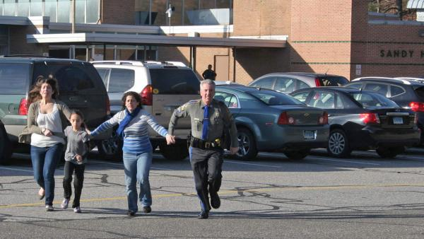 In this photo provided by the Newtown Bee, a police officer leads two women and a child from Sandy Hook Elementary School in Newtown, Conn., where a gunman opened fire, killing 26 people, including 20 children, Friday, Dec. 14, 2012.