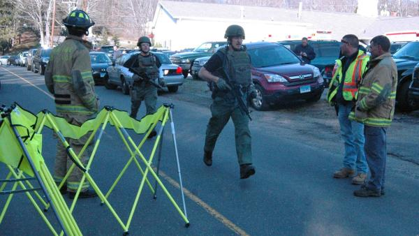 In this photo provided by the Newtown Bee, police officers are on the scene outside Sandy Hook Elementary School in Newtown, Conn., where authorities say a gunman opened fire, killing 26 people, including 20 children, Friday, Dec. 14, 2012.