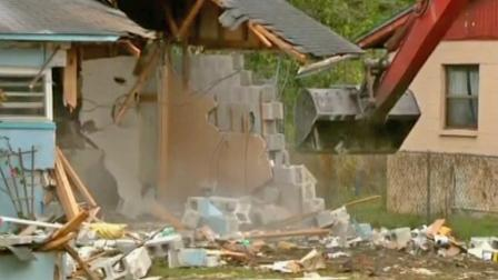Crews began the demolition of a Florida home over a sinkhole where a man is presumed dead after being swallowed by the earth. The demolition, seen above, started on Sunday, March 3, 2013.