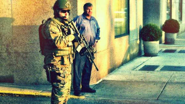 An armed guard patrols the street in Boston on Tuesday, Apri