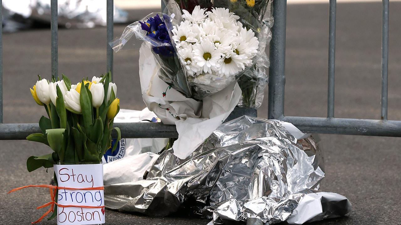 Flowers sit at a police barrier near the finish line of the Boston Marathon in Boston Tuesday, April 16, 2013. Explosions at the finish of the Marathon Monday killed at least 3 people and injured over 170.Winslow Townson
