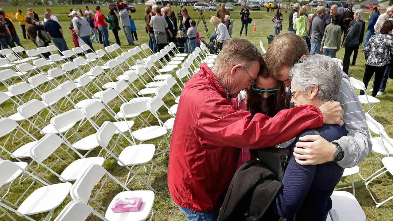Churchgoers huddle to pray after a service for the First Baptist Church in a field Sunday, April 21, 2013, four days after an explosion at a fertilizer plant in West, Texas.