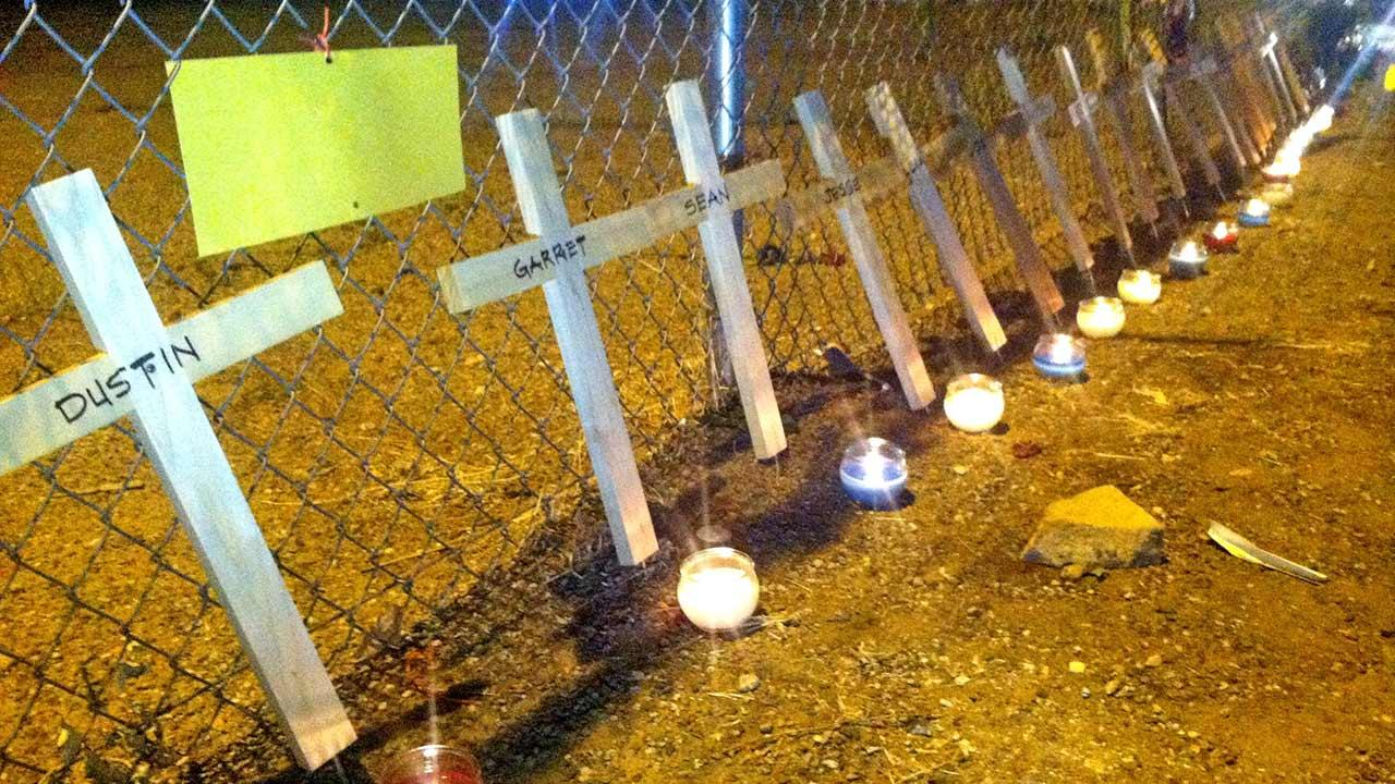Nineteen crosses and candles line a fence of Prescotts Fire Station 7 to honor the 19 firefighters killed while battling a wildfire near Yarnell, Ariz.