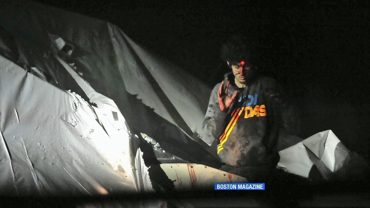Boston Marathon bombing suspect Dzhokhar Tsarnaev emerges from a covered boat as a sniper trains a laser target at his head. <span class=meta>(Boston Magazine)</span>