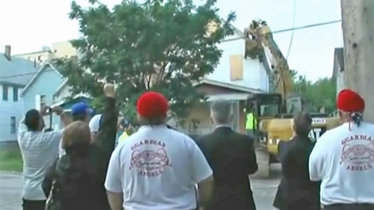 Spectators watch and cheer as Ariel Castros house is torn down in Cleveland Wednesday, Aug. 7, 2013.
