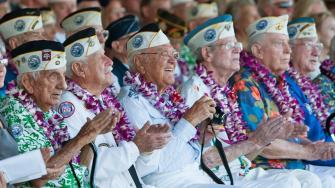 Pearl Harbor survivors watch a vintage WWII airplane fly over Pearl Harbor at the ceremony commemorating the 72nd anniversary of the attack on Pearl Harbor, Saturday, Dec. 7, 2013, in Honolulu.