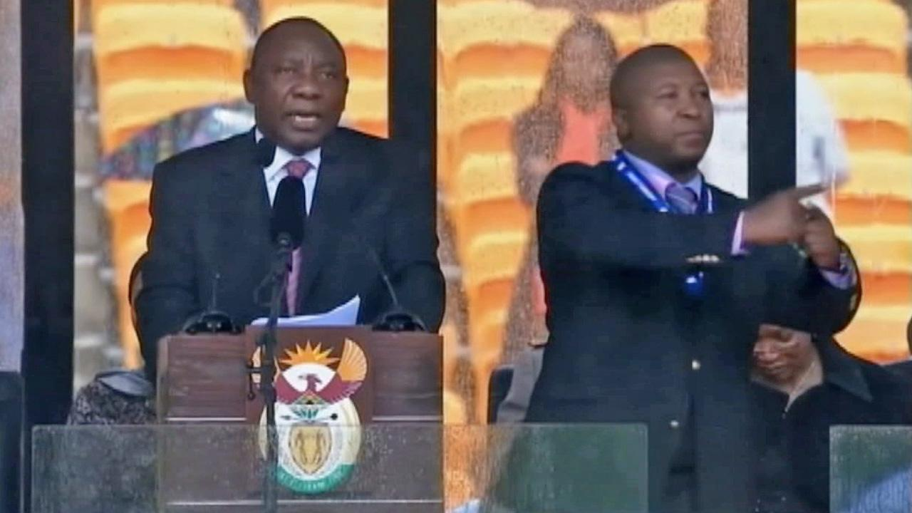Thamsanqa Jantjie (right) stands on stage during Nelson Mandelas memorial on Tuesday, Dec. 10, 2013. It was later found out that Jantjie was faking sign language during the ceremony.