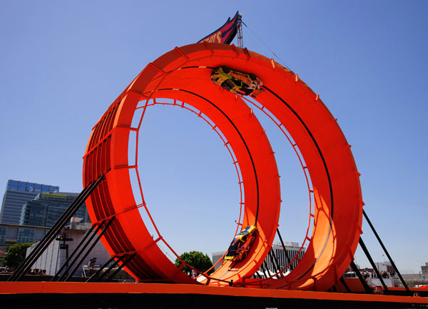 In this handout provided by Mattel, team Hot Wheels green driver Greg Tracy and yellow driver Tanner Foust set Guinness World Records Title by successfully racing through a 60-foot-tall double vertical loop at the X Games Los Angeles on Saturday June 30, 2012 in Los Angeles.  <span class=meta>(Photo by Max Simbron for Mattel&#47;Invision&#47;AP Images)</span>