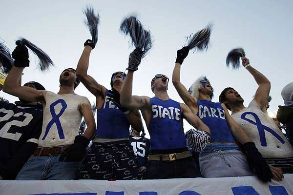 Fans cheer before an NCAA college football game...