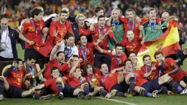 The Spanish team pose for photographers with the World Cup trophy, center foreground, following the World Cup final soccer match between the Netherlands and Spain at Soccer City in Johannesburg, South Africa, Sunday, July 11, 2010. Spain won 1-0