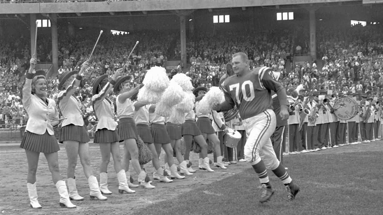 Baltimore Colts veteran defensive tackle Art Donovan races onto field on Sept.16, 1962 to the salute of Colts drum majorettes and cheerleaders as he was honored prior to the Baltimore-Los Angeles Rams game.