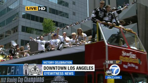 Los Angeles Kings players and their family wave from atop a bus during a parade celebrating the team's NHL hockey Stanley Cup championship in Los Angeles, Thursday, June 14, 2012.