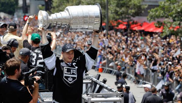 Los Angeles Kings' Dustin Brown hoists the Stanley Cup during a parade celebrating the team's NHL hockey Stanley Cup championship in Los Angeles, Thursday, June