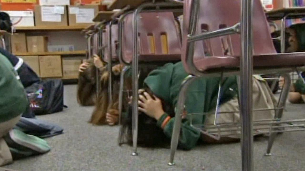 Students cover their heads during an earthquake drill in this undated file photo.