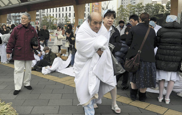 Patients and nurses evacuated from a hospital stay outside the building in Sendai, Miyagi Prefecture, Friday, March 11, 2011 after a powerful tsunami spawned by the largest earthquake in Japan's recorded history slammed the eastern coast.