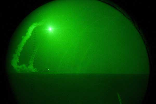 Seen through night-vision lenses aboard amphibious transport dock USS Ponce, the guided missile destroyer USS Barry fires Tomahawk cruise missiles in support of Operation Odyssey Dawn.