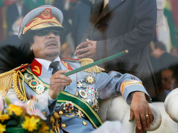 "<div class=""meta ""><span class=""caption-text "">In this Tuesday, Sept. 1, 2009 file photo, Libyan leader Moammar Gadhafi gestures with a green cane as he takes his seat behind bulletproof glass for a military parade in Green Square, Tripoli, Libya. Gadhafi was killed Thursday, Oct. 20, 2011 by rebel forces in Sirte. (AP Photo/Ben Curtis)</span></div>"