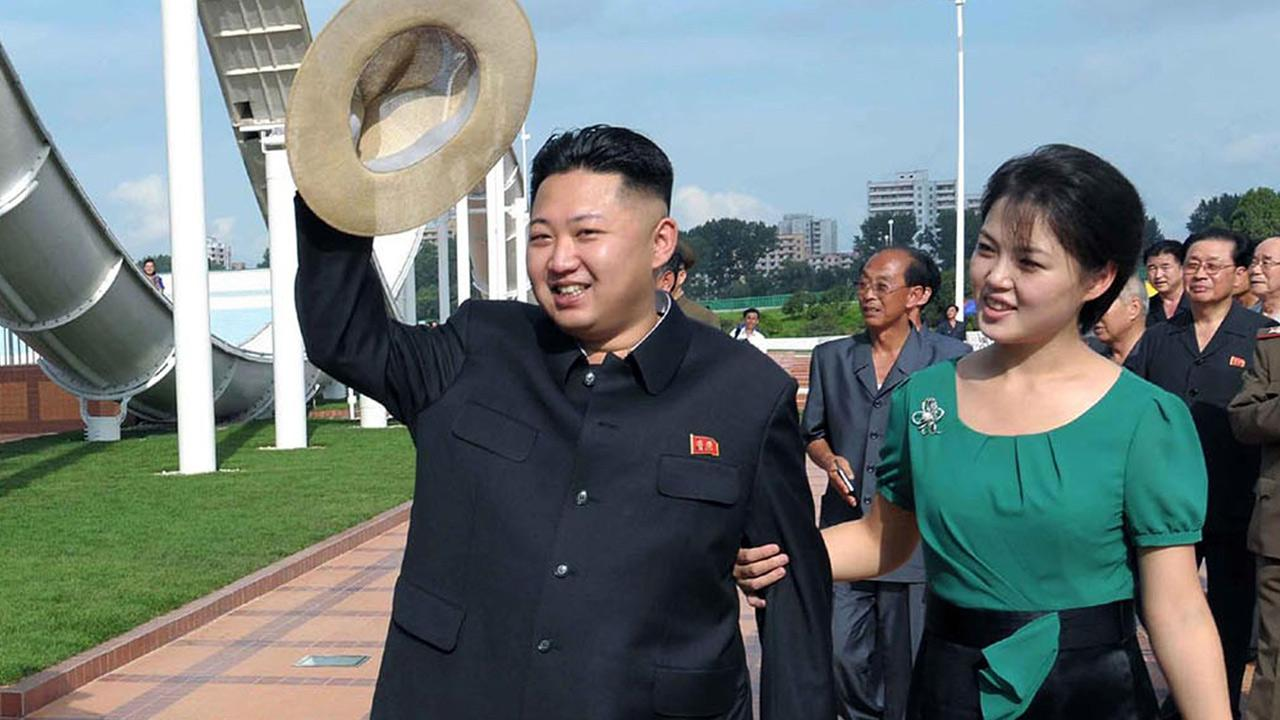 In this July 25, 2012 file photo released by the Korean Central News Agency and distributed in Tokyo by the Korea News Service, North Korean leader Kim Jong Un, accompanied by his wife Ri Sol Ju, waves to the crowd.