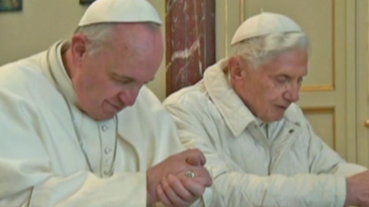 Pope Francis, left, and Pope emeritus Benedict XVI, right, are seen praying side-by-side at chapel Castel Gandolfo on Saturday, March 23, 2013.