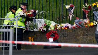 Police officers lay down floral tributes handed to them by members of the public at the scene of a terror attack in Woolwich, southeast London, Thursday, May 23, 2013.