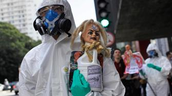 A protester wearing a protective suit and mask holds up a bottle of Monsantos Roundup herbicide during a protest against Monsanto in Sao Paulo, Brazil, Saturday, May 25, 2013.