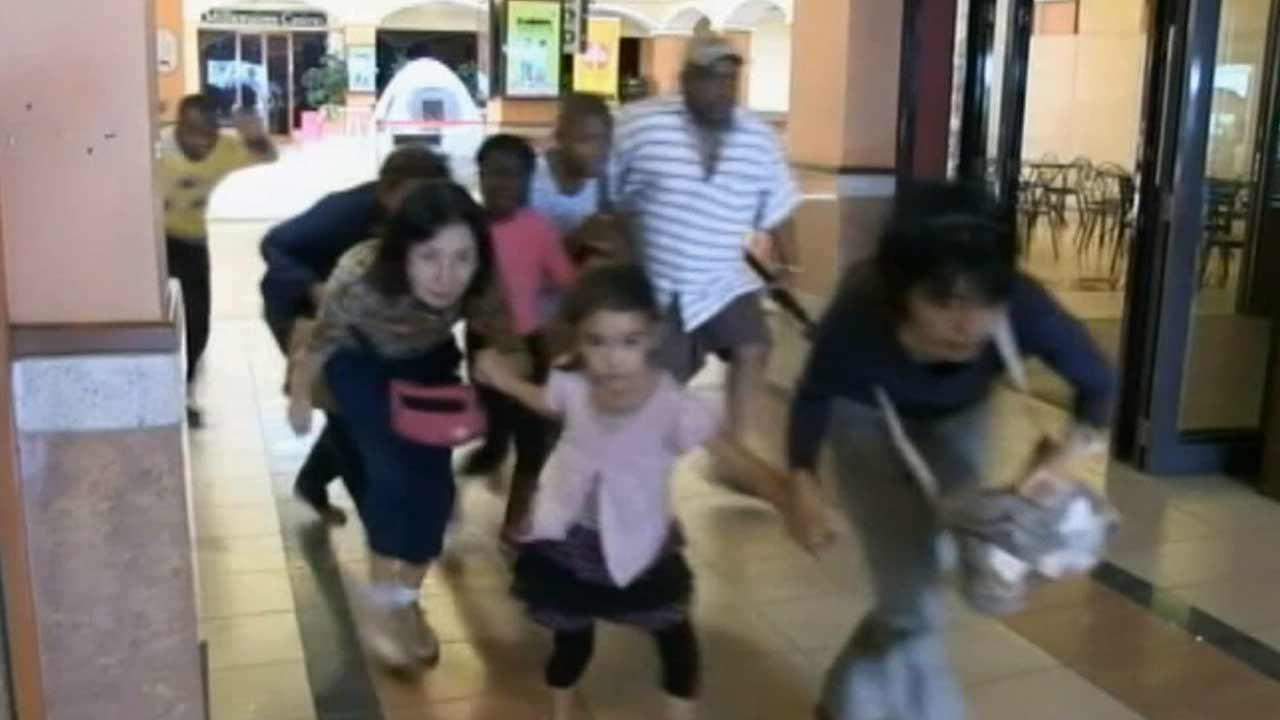 People are seen running out of Westgate mall in Nairobi, Kenya, as Kenya forces attempt to end a three-day siege by al-Shabab attackers on Monday, Sept. 23, 2013.