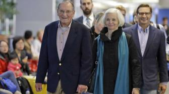 Merrill Newman, left, walks beside his wife Lee and son Jeffrey after arriving at San Francisco International Airport, Saturday, Dec. 6, 2013, in San Francisco.
