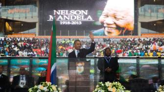 President Barack Obama waves as he arrives to speak to crowds attending the memorial service for former South African president Nelson Mandela at the FNB Stadium in Soweto near Johannesburg, Tuesday, Dec. 10, 2013.
