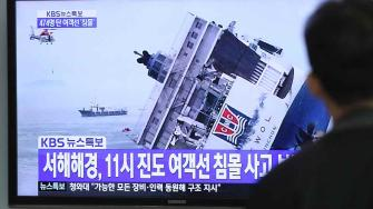 A man watches a TV news program showing a sinking passenger ship, at Seoul Railway Station in Seoul, South Korea, Wednesday, April 16, 2014.