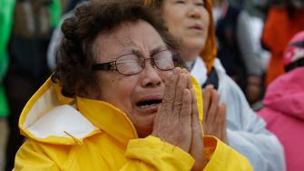 One of relatives of passengers aboard a sunken ferry cries during a Buddhist ceremony to pray for speedy rescue and their safety at a port in Jindo, south of Seoul, South Korea, Friday, April 18, 2014.
