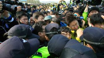 Relatives of missing passengers aboard the sunken ferry Sewol struggle with policemen as they try to march toward the presidential house to protest the governments rescue operation in Jindo, South Korea, Sunday, April 20, 2014.