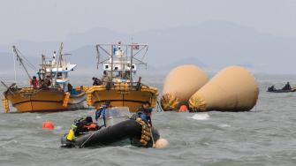 South Korean rescue team members work to rescue passengers believed to have been trapped in the sunken ferry Sewol near the buoys which were installed to mark the vessel in the water off the southern coast near Jindo, South Korea, Monday, April 21, 2014.