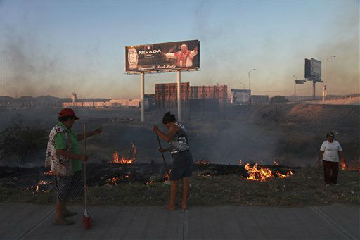 Women sweep an area by a field where billboards from a watch company welcome Pope Benedict XVI near the airport in Leon, Mexico, Thursday March 22, 2012.